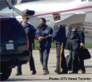 Suspect is led from plane to van by RCMP
