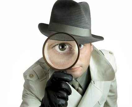 A detective looking through a magnifing glass