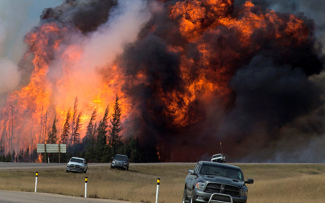 Fort McMurray wildfire with abandoned vehicles in foreground