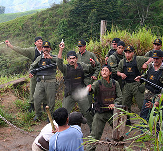 Guards confront villagers protesting a Canadian-financed mine in Ecuador