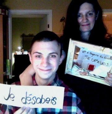 "Image: Mother and son with signs: ""Je desobeis"""