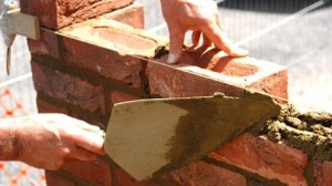 Cement being applied to a brick wall with a trowel