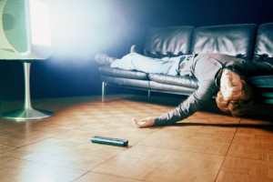 Man Lying on Sofa in Front of TV
