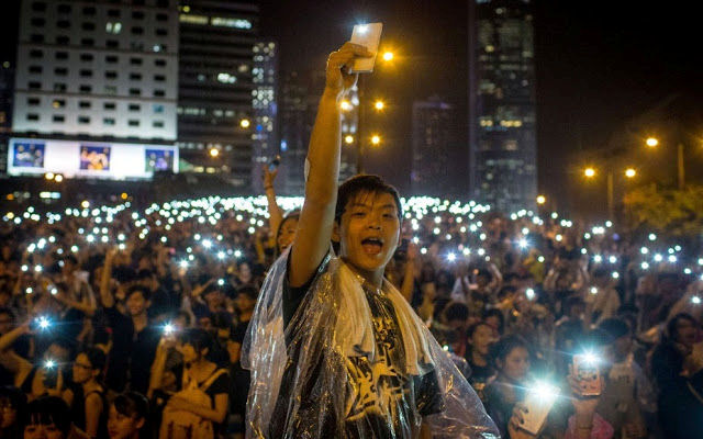 Protestor holding up phone with light on